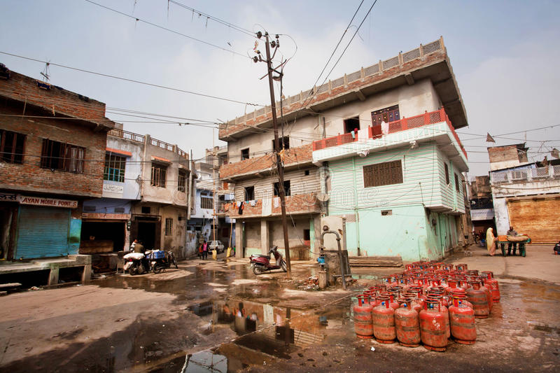 Pålagda gascylindrar en smutsig gata med gamla hus av fattiga familjer arkivfoton