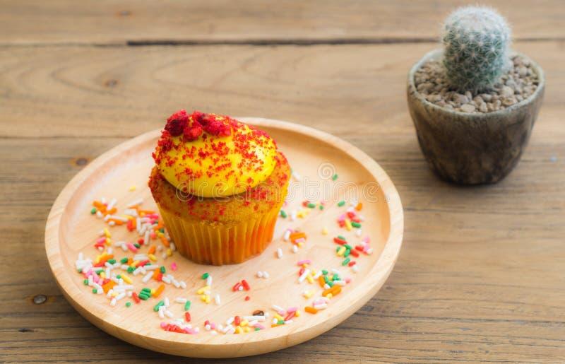 Pålagda gula muffin en sfärisk träplatta Strilat med att överträffa många färger arkivfoton