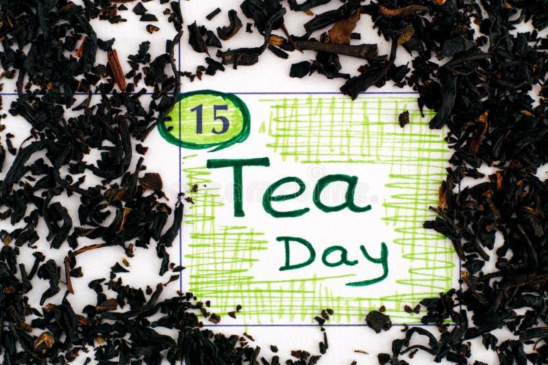 Påminnelse av teadagen i kalendern med spill av torkade teblad royaltyfria foton