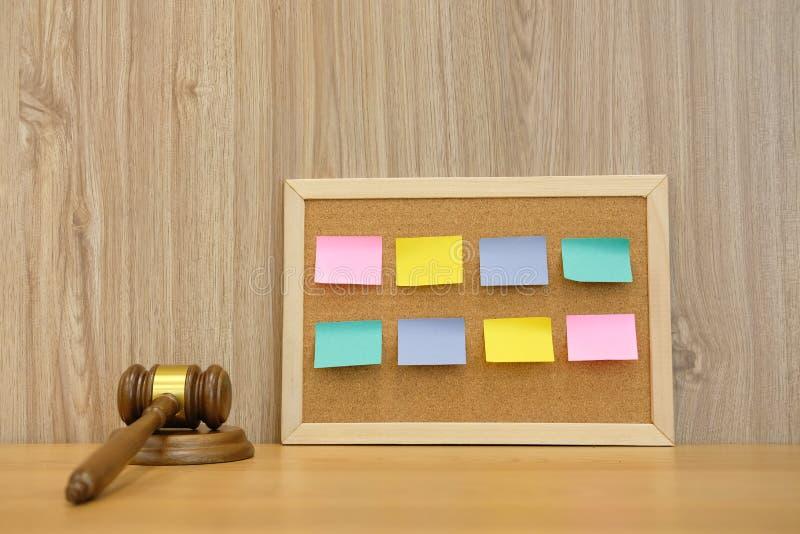 påminnelse för papper för anmärkningar för domareauktionsklubba klibbig på korkbräde advokat på arkivfoto