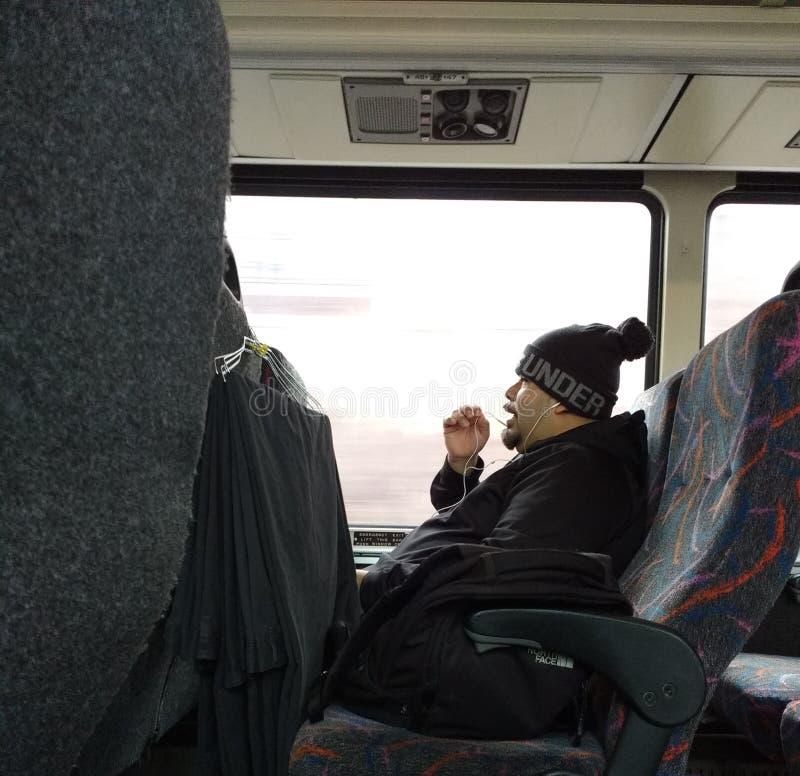 Påringning, medan rida bussen, pendlare som talar på en mobiltelefon som är ny - ärmlös tröja, USA royaltyfri fotografi