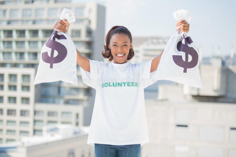 Påsar för pengar för lycklig volontärkvinna hållande royaltyfria bilder
