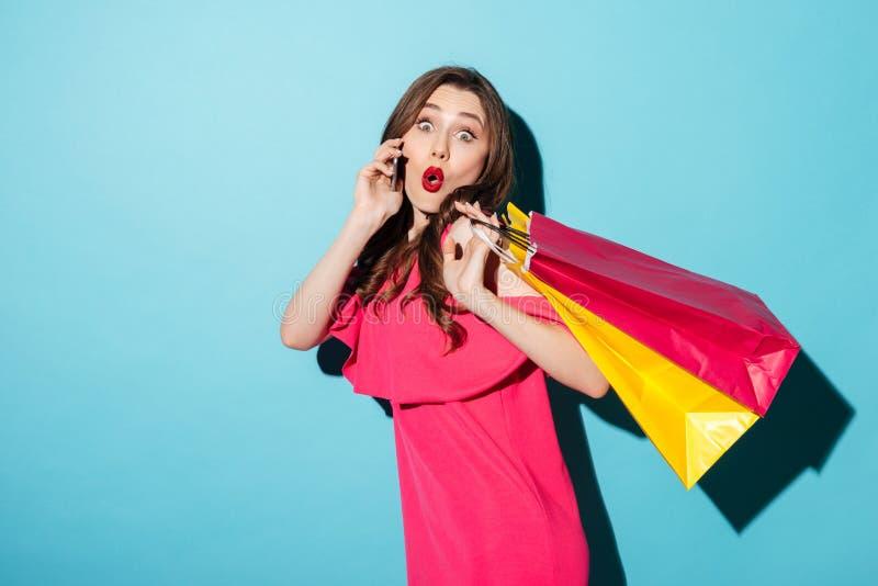 Påsar för shopping för chockad ung brunettdam som hållande talar vid telefonen arkivfoto
