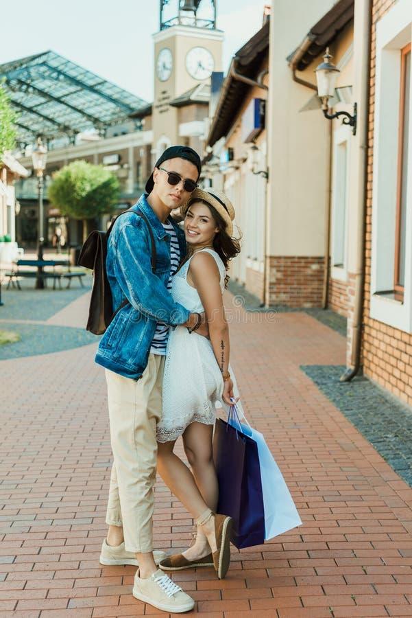 Påsar för shopping för unga hipsterpar hållande och krama på gatan royaltyfri bild