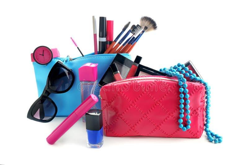 Påsar med dekorativa skönhetsmedel och makeupborstar på vit bakgrund royaltyfri foto