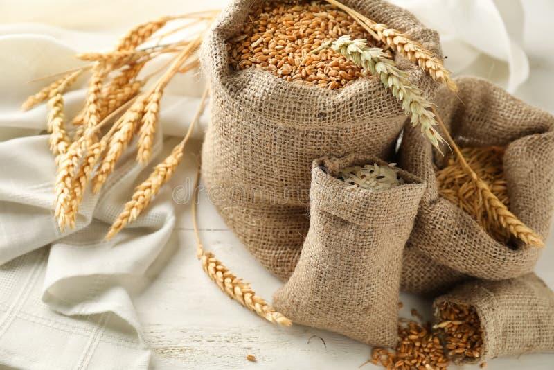 Påsar med rått vete, havre och ris på den vita trätabellen arkivbilder