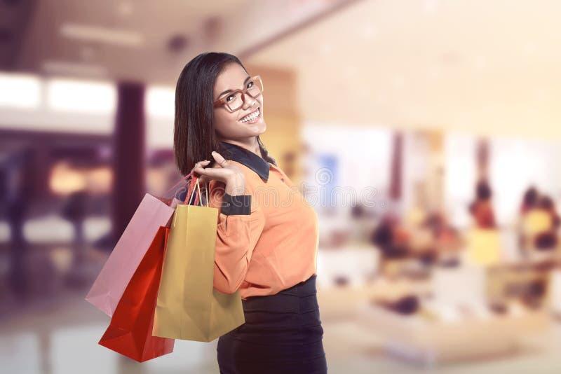 Påsar och le för shopping för lycklig asiatisk kvinna hållande royaltyfria foton