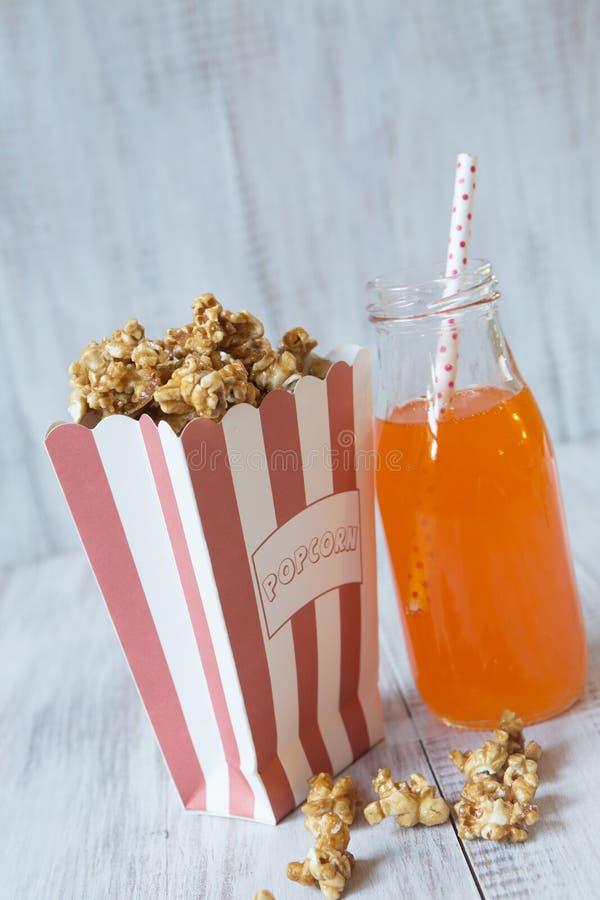 Påse av karamellpopcorn med pop för orange sodavatten fotografering för bildbyråer
