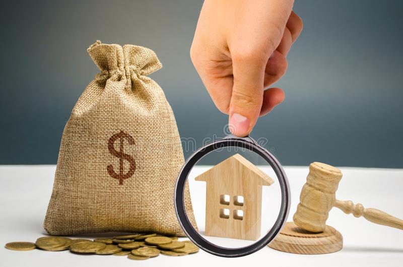 Påse av pengar, huset och auktionsklubban Beslag av icke-betalning för egenskap tack vare av skatter Egenskapsavlägsnande Skatter arkivfoto