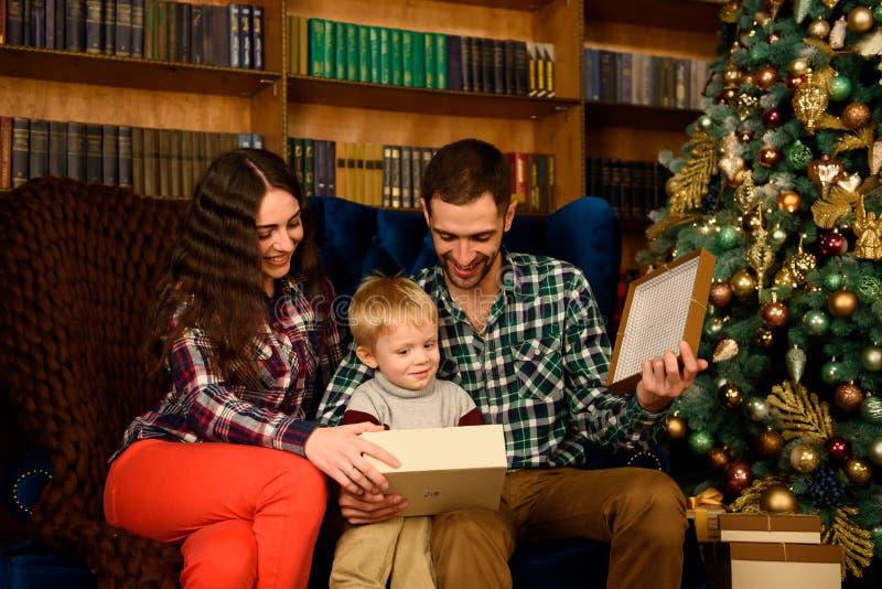 Påse för gåva för julfamilj som öppen närvarande ser till magiskt ljus i inre för nattXmas-träd royaltyfria foton