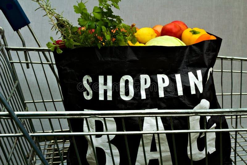 Påse för shopping för självbetjäningsupermarket full i spårvagndiagram arkivfoton