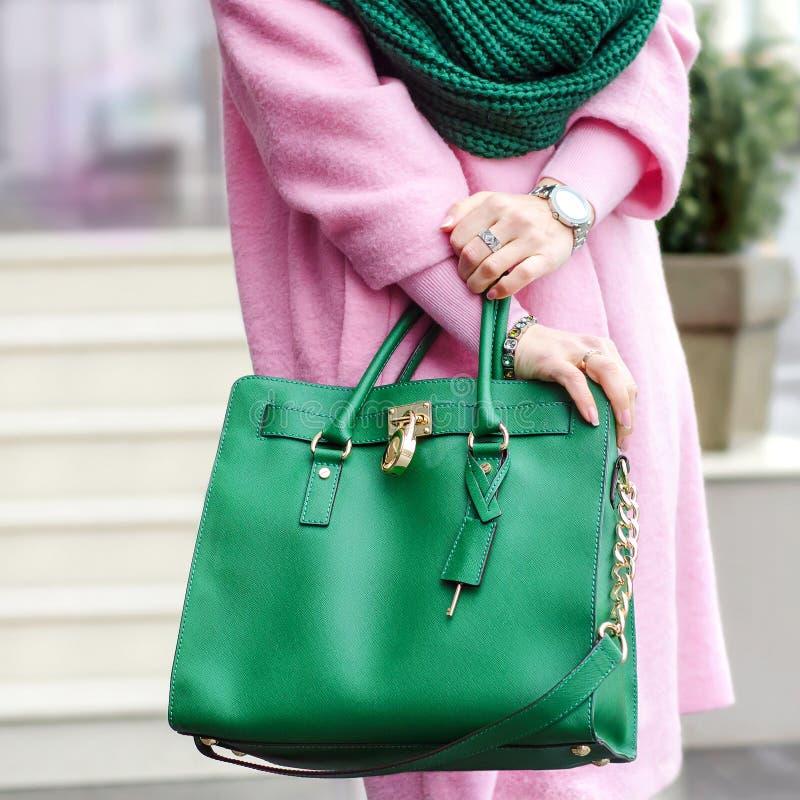 Påse i kvinnliga händer Ljus läderpåse _ Rosa färger täcker och gör grön påsen arkivbilder