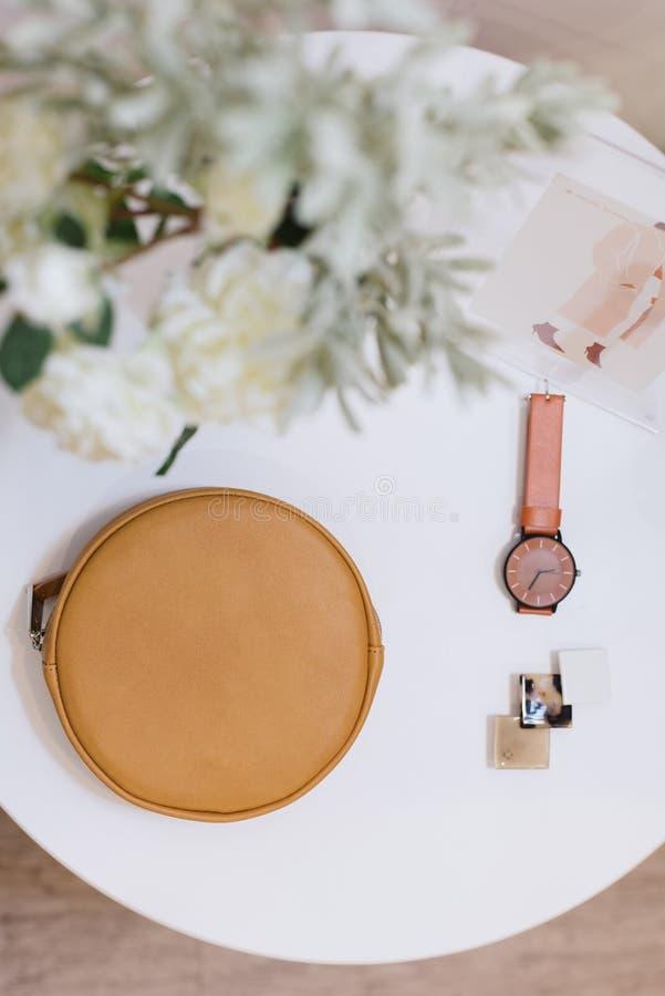 Påse-, klocka- och hårspännelögn på en vit tabell royaltyfri fotografi