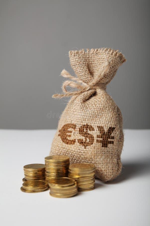 Påse med den pengar- och yuan-, dollar- och eurokonturn på grå bakgrund Symbol av rikedom och h?ga vinster royaltyfria bilder