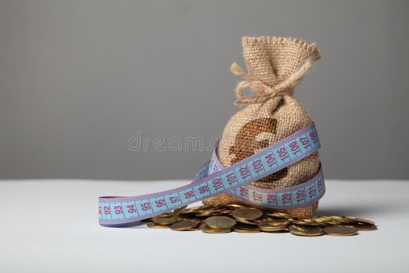 Påse med pengar och mätabandet på guld- mynt Brist av pengar, armod och besparingar arkivbilder