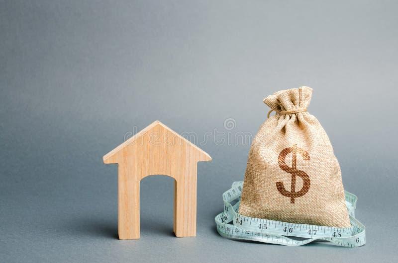 Påse med pengar och måttband med ett trähus Begreppet av en inskränkt fastighetbudget Låga subventioner Brist av royaltyfria foton