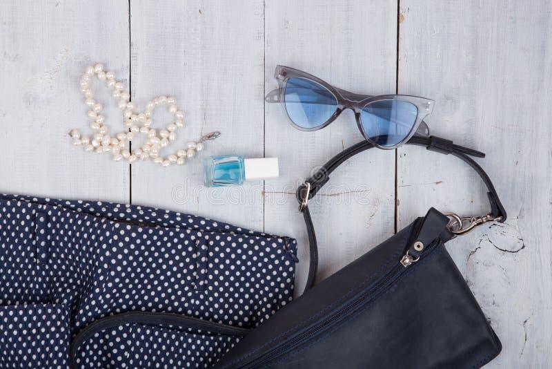 Påsen byxa, solglasögon, spikar polermedel, pärlasmycken på vit träbakgrund royaltyfri bild