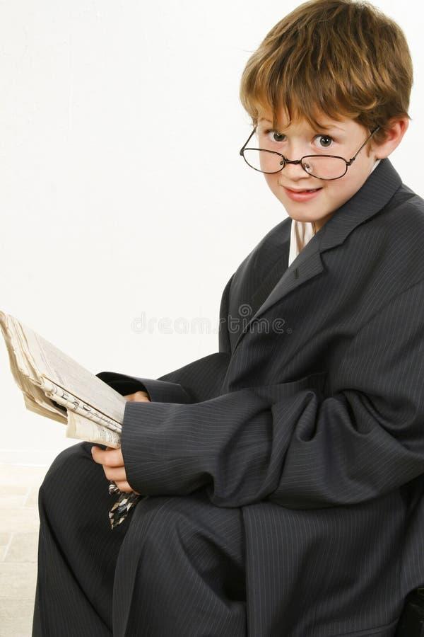 påsig dräkt för pojketidningsavläsning royaltyfria foton