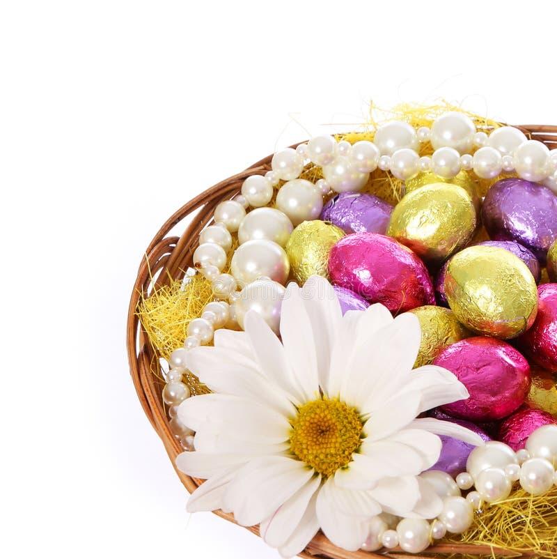 Påskägg, färgrika chokladägg med chamomilen blommar och pryder med pärlor halsband i korg arkivbild