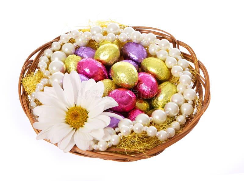 Påskägg, färgrika chokladägg med chamomilen blommar och pryder med pärlor halsband i korg fotografering för bildbyråer