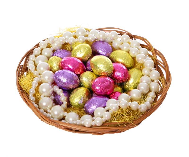 Påskägg, färgrika chokladägg och pärlemorfärg halsband i korg royaltyfri bild