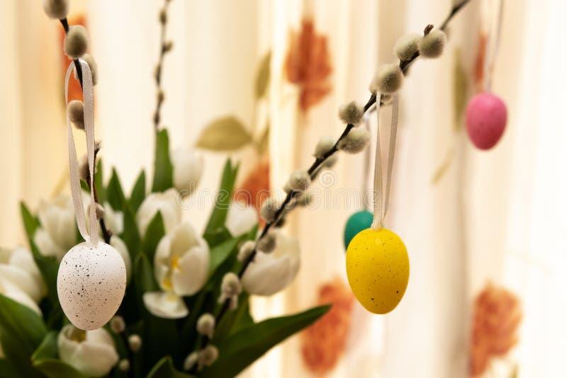 Påskägg i buketten av blommor, slut upp av färgrika påskägg arkivfoton