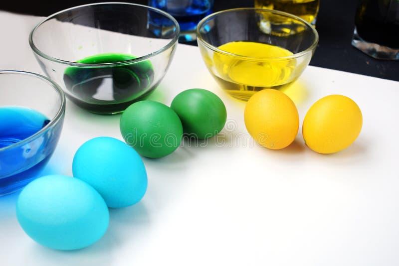 Påskägg med koppar av målarfärg Vårferie Gula, gröna och blåa ägg royaltyfria bilder