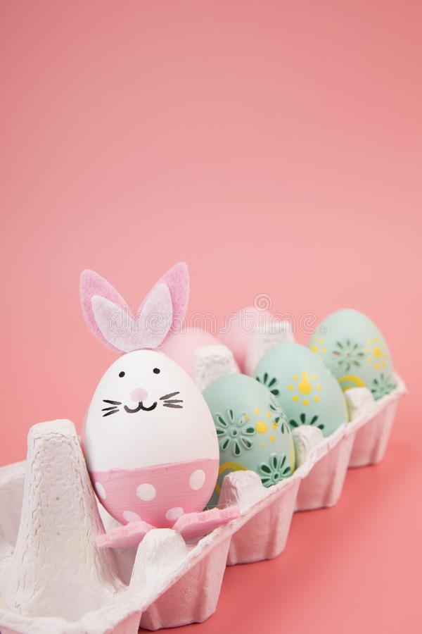 Påskägg med rosa tema i gåvaasken ägget dekoreras som en gullig kanin som spelar med en annan kanin, på en rosa backgroun royaltyfri fotografi