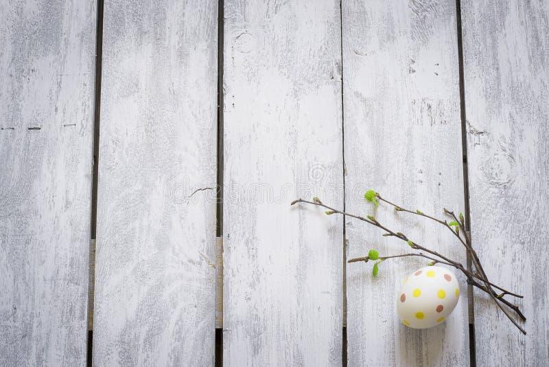 Påskägg och ris med unga sidor på lantliga träplankor royaltyfri fotografi