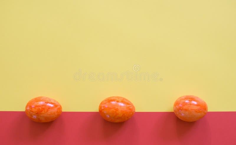 Påskägg på gul och röd bakgrund fotografering för bildbyråer