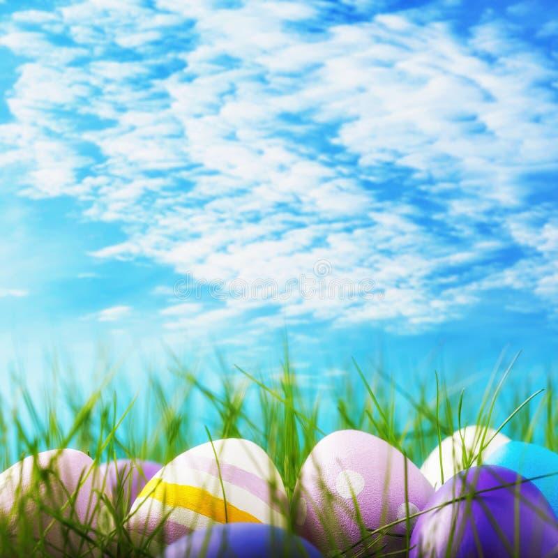 Påskägg som dekoreras i olika färger i gräset mot himlen fotografering för bildbyråer