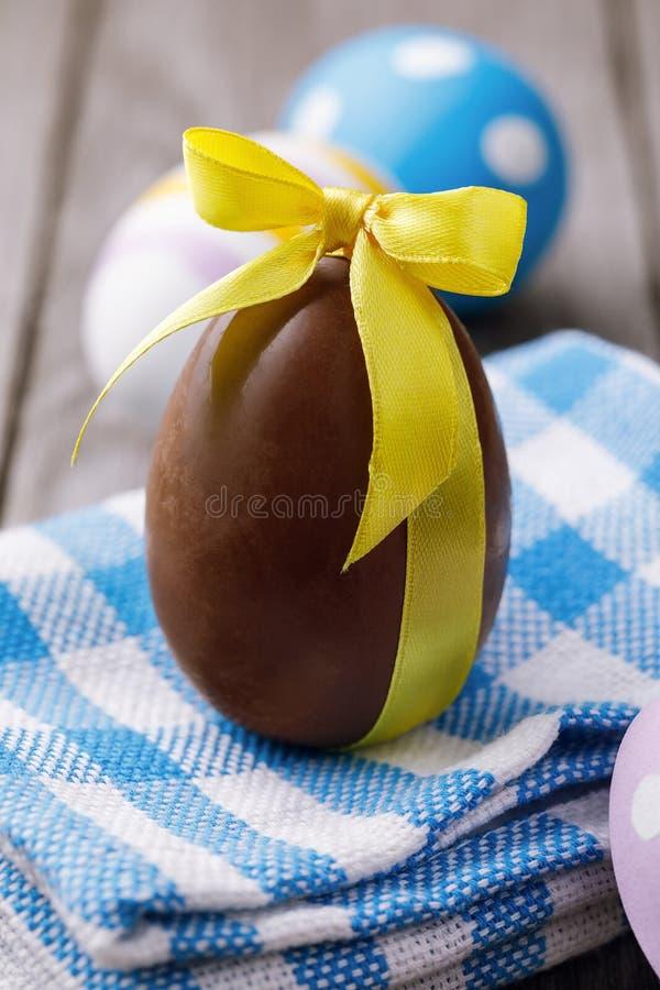 Påskägg som göras av choklad, bundet med ett gult band royaltyfria foton