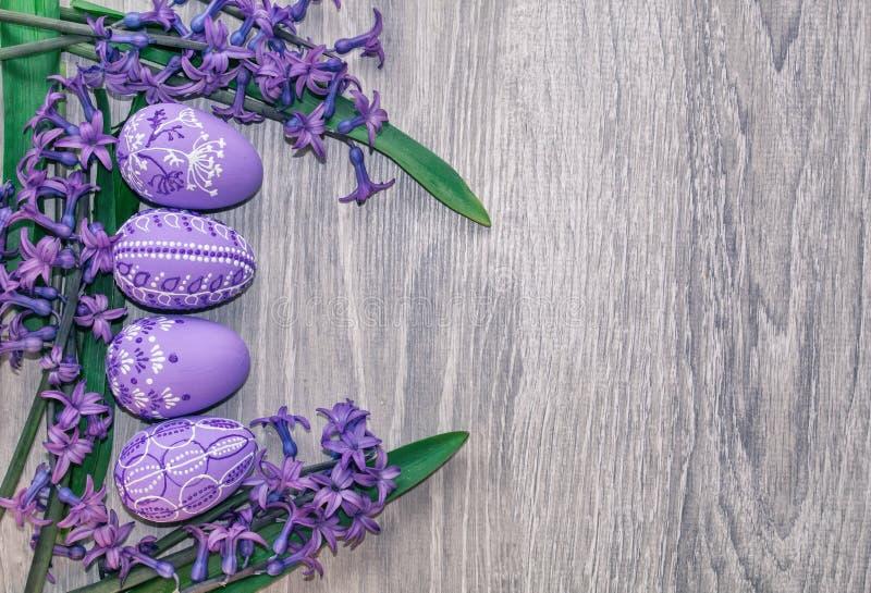 Påskägg som målas med blommor i lila signaler, på träbakgrund med utrymme för fri text fotografering för bildbyråer