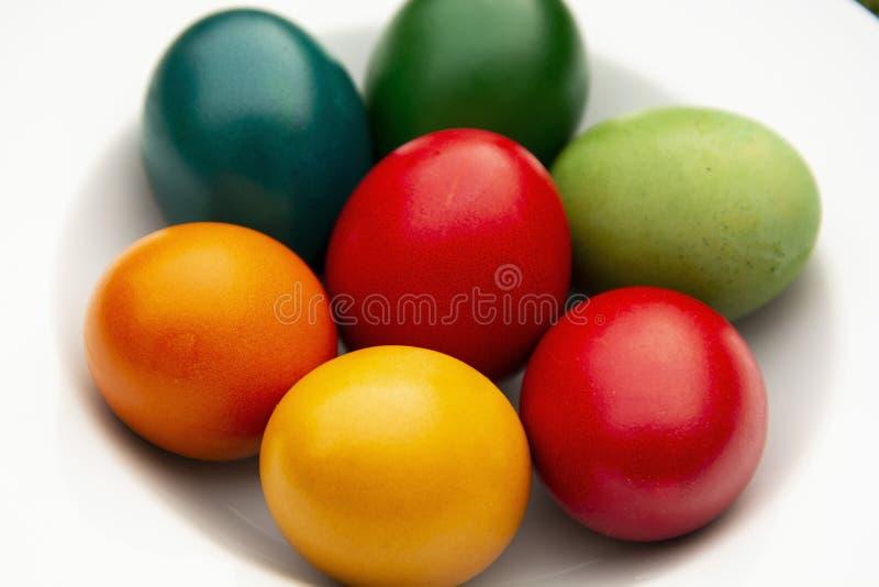 Påskägg traver i den vita plattan Färgrika, röda, gröna, blåa, gula och orange ägg Top beskådar royaltyfria foton