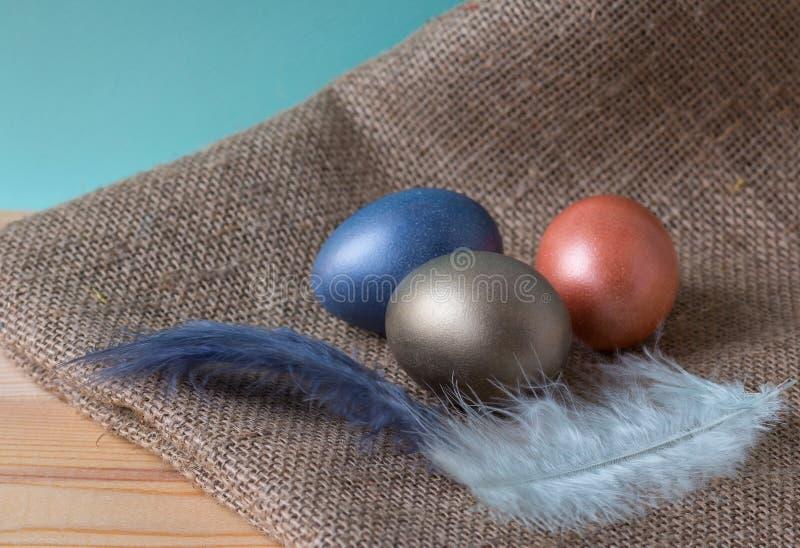 Påskägg tre färger på säckväv på en trätabell arkivbilder