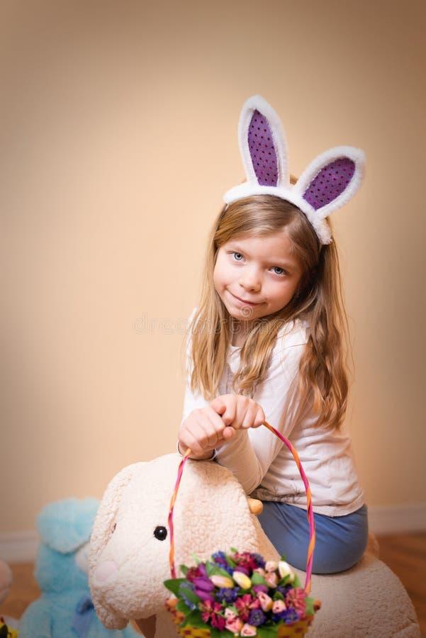 Påsk! Den förtjusande lilla flickan med kaninöron rymmer en korg med blomman arkivbilder