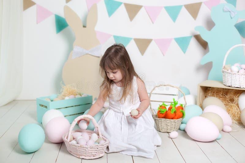 Påsk! Den härliga lilla flickan i en vit klänning lägger påskägg i en korg Många olika färgrika påskägg, färgrik interio arkivbild