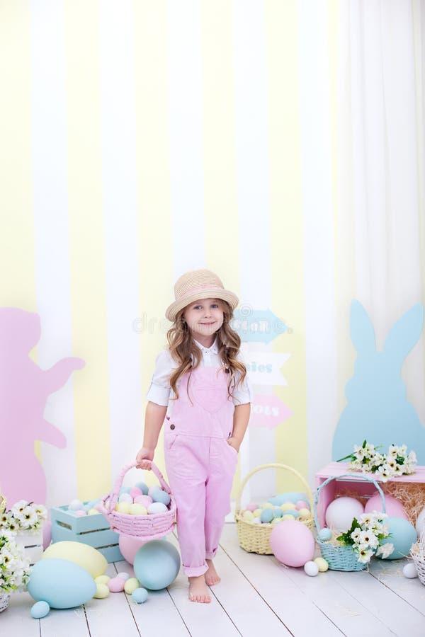 Påsk! En gullig flicka är stå och rymma en korg med ägg i hennes händer med en garnering i bakgrunden Påskdekor, fa arkivfoton