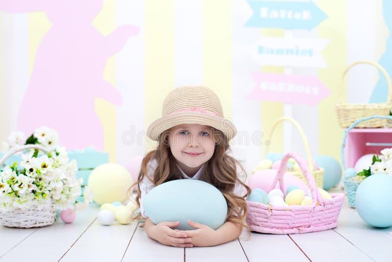 Påsk! Gullig flicka som spelar med det easter ägget Ett barn rymmer ett stort färgrikt ägg på bakgrunden av påskinre Påskcolorfu arkivbild