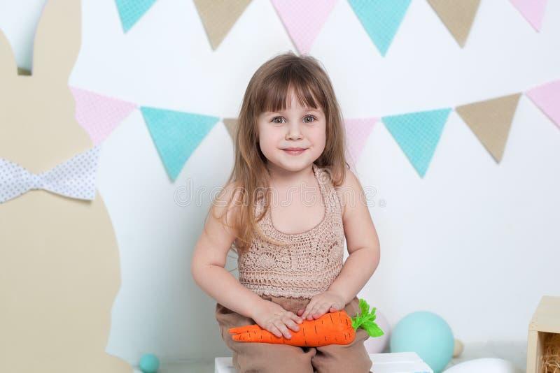 Påsk! Härlig liten flicka på en vit bakgrund med moroten, färgrika ägg, korgen och hare Påskläge, påskdecorati arkivfoto