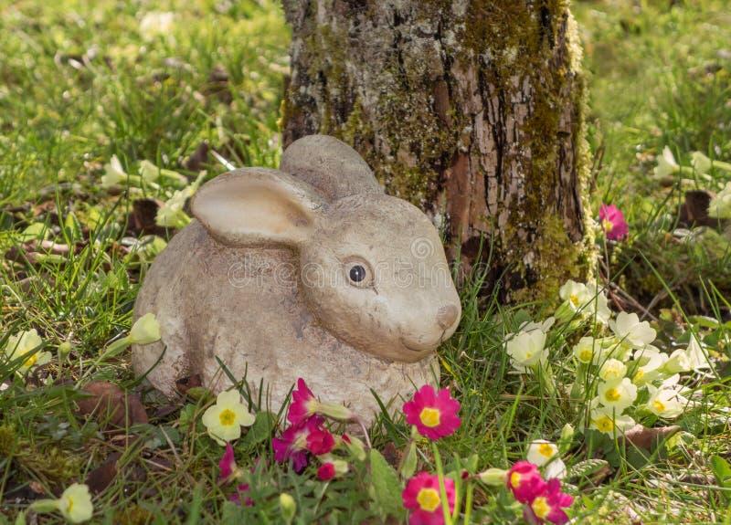 Påsk - kanin som göras av keramiskt i den blommande trädgården arkivfoton
