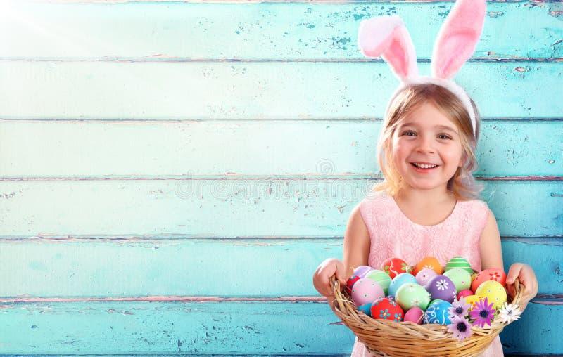 Påsk - liten flicka med korgägg och Bunny Ears royaltyfri bild