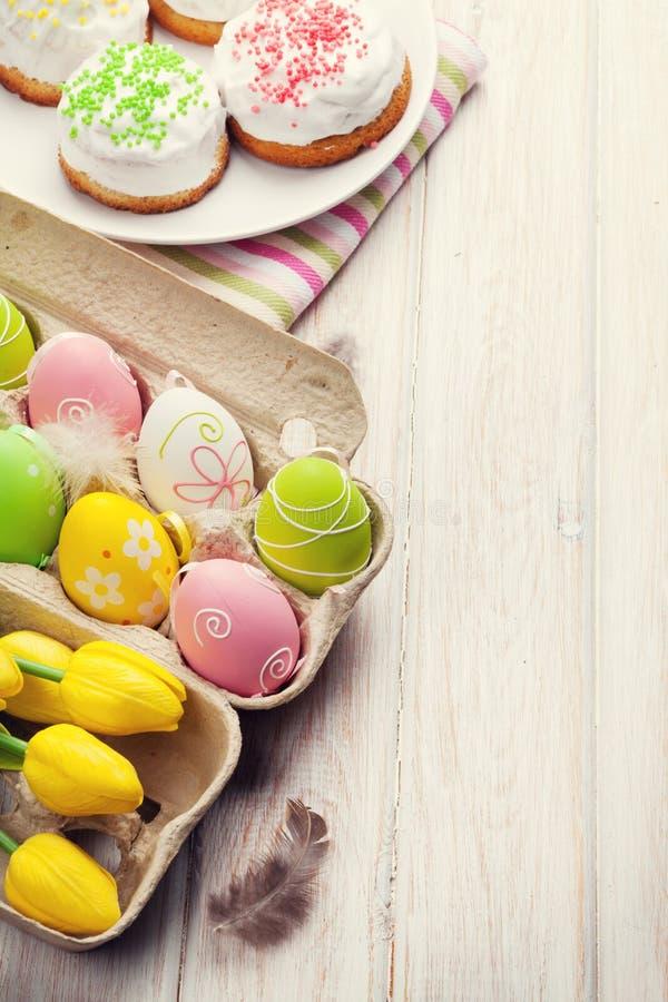Påsk med gula tulpan, färgrika ägg och traditionella kakor royaltyfria foton