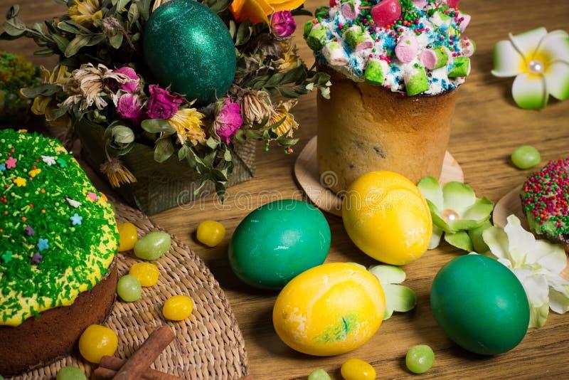 Påsk som firar familjmatställen, färgägg, kakor, fruktte, sötsaker royaltyfri bild
