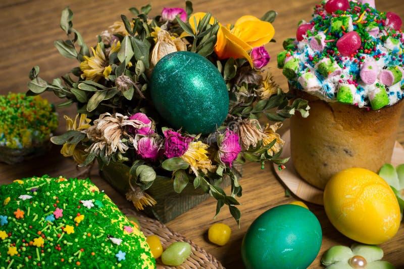 Påsk som firar familjmatställen, färgägg, kakor, fruktte, sötsaker arkivfoton