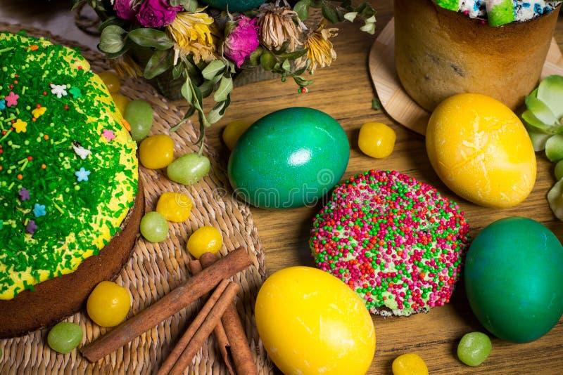 Påsk som firar familjmatställen, färgägg, kakor, fruktte, sötsaker royaltyfri fotografi