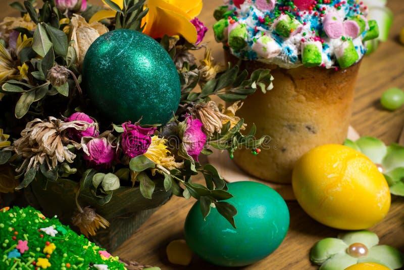 Påsk som firar familjmatställen, färgägg, kakor, fruktte, sötsaker arkivfoto