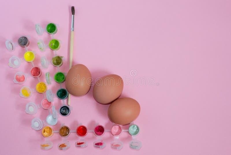 Påskarbetsställe som förbereder sig för att måla fega ägg för ferie på rosa bakgrund med copyspace arkivbild