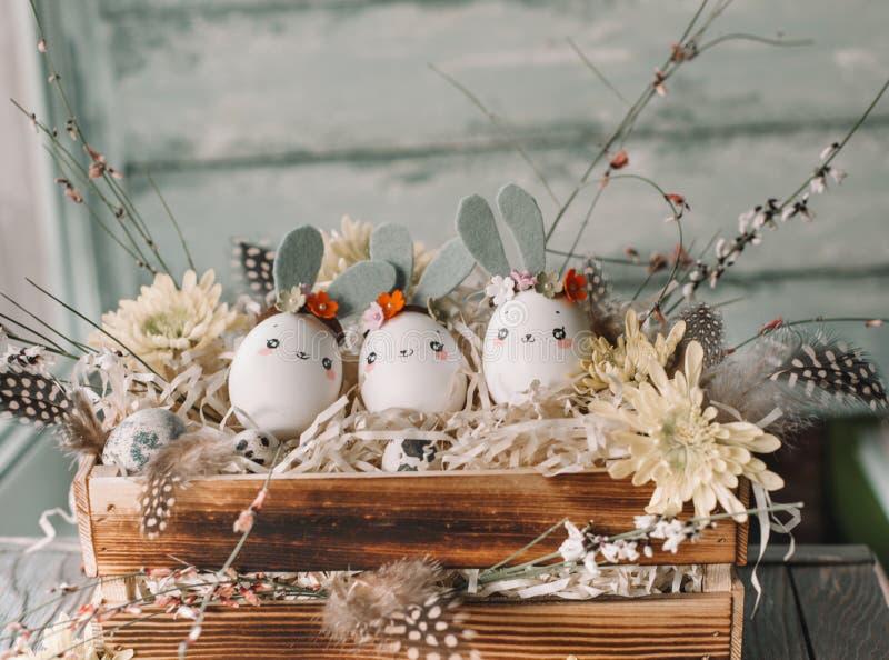 Påskbakgrund, hemlagade äggskalstunna kaniner och gul krysantemum i träask royaltyfri foto