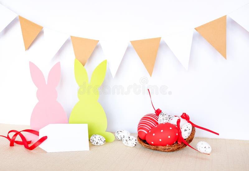 Påskbakgrund med ägg, kaniner och girlandflaggor arkivbilder